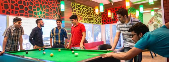 Young male students play pool in the UFV student lounge