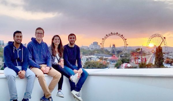 Four students sitting on a ledge in Vienna